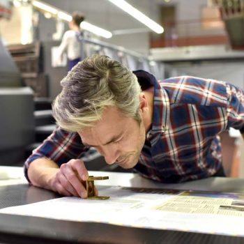Drucker an Leuchttisch einer Druckmaschine überprüft Druckbogen