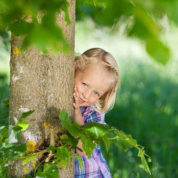 Kind versteckt sich hinter Baum