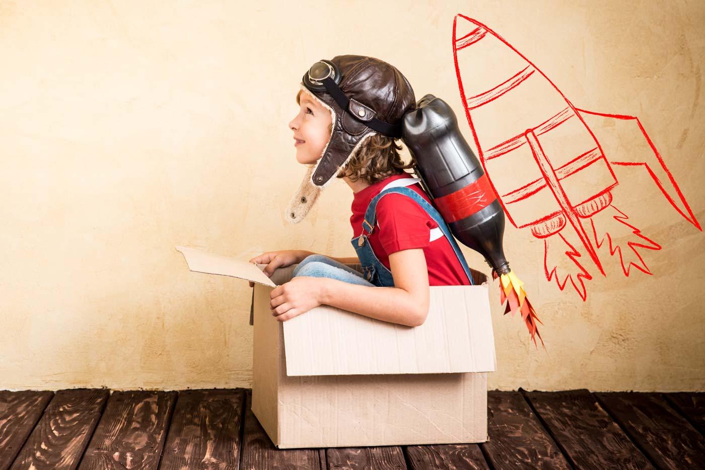 Kind mit Raketenrucksack sitzt in einem Karton